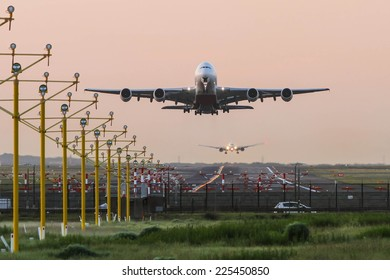 Airbus A380 airliner taking off while second jet lands in background