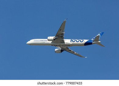 AIRBUS PLANT, BLAGNAC AIRPORT, TOULOUSE, FRANCE - OCTOBER 12, 2017: prototype of modern passenger aircraft Airbus A350-1000 XWB performs a test flight. The plane is climbing in the blue sky.