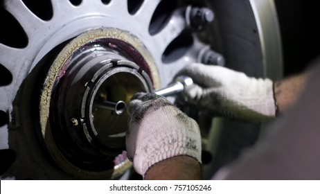 Aircraft brake repair. Close up of airplane wheel and shaft. Huge airplane tyre with shaft and landing gear of plane under airplane. Engineer fixing aircraft's wheel