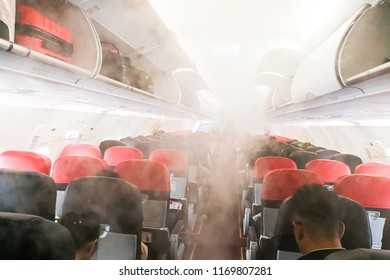 Aircraft cabin with smoke-like air vapor condensation due to differences of temperature between cabin and outside.