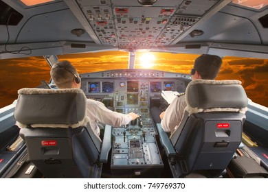 Aircraft cockpit in flight. The pilots at work. Sunset sky view.
