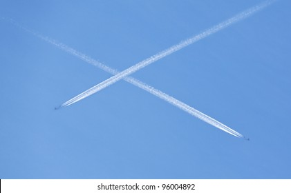 Aircraft contrails crossing and forming an X in a blue sky