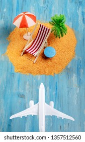 Aircraft and dream island. Miniature beach with deckchair, palm and umbrella on blue background. Vacation and exotic travel concept