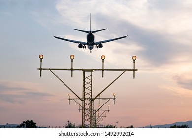 Aircraft during the approach procedure at sunset overflying the runway lights. Precision approach ILS-guided landing.