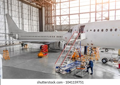 Aircraft during repair, technical inspection is a working technician. View of nose, a cockpit with a staircase leading into the entrance. In background, the other tail and fuselage of the airplane