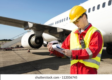 Aircraft engineer with a checklist of several pages on a clipboard