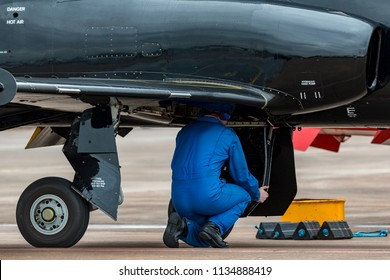 Aircraft engineer working in the undercarriage bay of a military jet trainer.