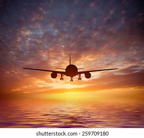 aircraft flies over the ocean on a background of a magnificent sunset