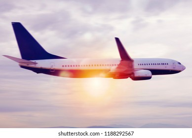 Aircraft flight over the clouds during sunrise