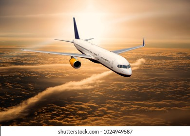 Aircraft in flight. The passenger plane flies high above the clouds during the sunset.
