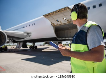 Aircraft ground handling. Man in headphones observing airplane with open cargo door and intending to fill out documents. Copy space in left side