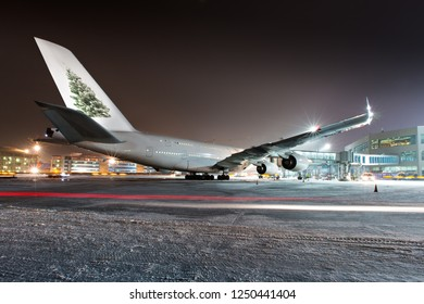 Aircraft with the image of a Christmas tree on the keel. Double-decker passenger plane parked near airport terminal at night. The airplane rear view.