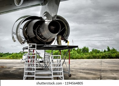 Aircraft inspector standing at the engine for maintenance service check and repair if required.Aircraft inspector inspection combustion,turbine blade of jet engine by borescope camera with tripod .