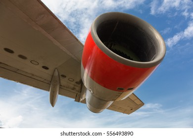 Aircraft jet engine beneath large wing with clear blue sky.