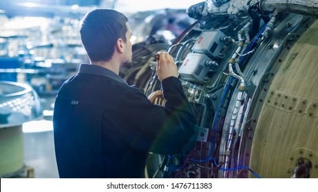 Aircraft Maintenance Mechanic Inspecting with Flashlight Airplane Jet Engine in Hangar