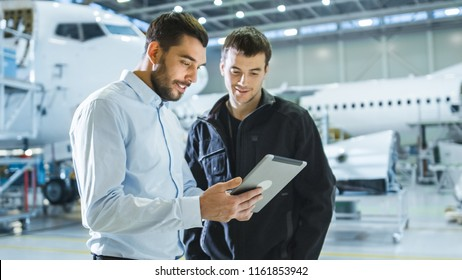 Aircraft Maintenance Worker and Engineer having Conversation. Holding Tablet.