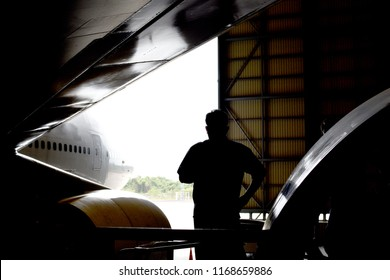 Aircraft mechanic standing under wing of aircraft (airplane) wing for check crack, dent ,corrosion in aircraft hangar for maintenance service check before flight.