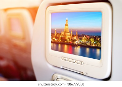 Aircraft monitor in front of passenger seat showing  Wat Arun night view Temple in bangkok, Thailand background