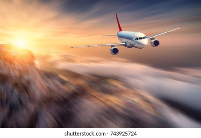 Aircraft with motion blur effect is flying over low clouds at sunset. Landscape with passenger airplane, blurred clouds, mountains, sun. Passenger airplane. Business travel. Commercial plane. Concept