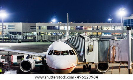 aircraft parked at the airport and preparation for next flight. Loading cargo on the plane in airport terminal at night. Workers cargo airplane service.