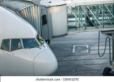 Aircraft with passage corridor/tunnel being prepared for departure from an international airport - Passangers boarding an airplane in a modern airport