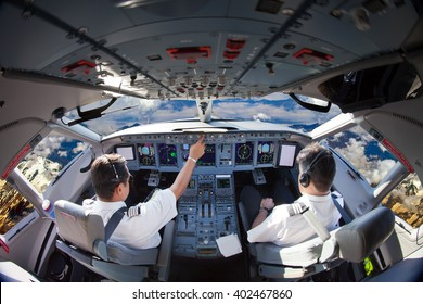 The Aircraft pilots at work. Plane is flying over the mountains. View from the cockpit.