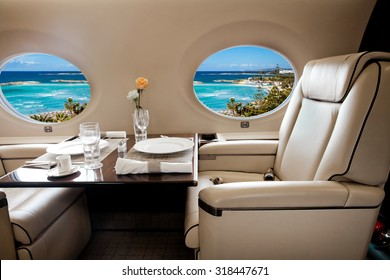Aircraft porthole with view of sea and beach resort, flight by business class