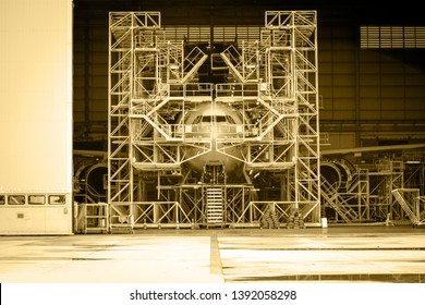 Aircraft push back into the maintenance area.Airplane parking in hangar for maintenance service check by aircraft technician.Aircraft Docking and Maintenance Platforms in front of airplane.