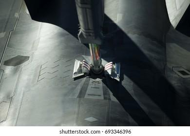 An aircraft receives fuel in midair through a boom stick.