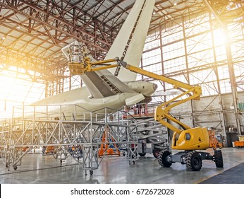 Aircraft service, view of the tail of the aircraft and a crane with a human technician