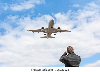 Aircraft spotting concept. Man is looking at landing plane and taking a photo / video. Airplane at sky with white clouds.