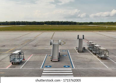 Aircraft stairs and baggage trolleys stored at an empty airport, no traffic, no flights coming
