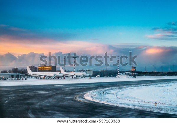 Aircraft stand on ground at International Airport terminal in early morning with beautiful sunrise dramatic sky.