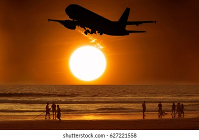 Aircraft take off and the sunset and people on the beach.