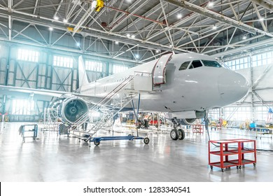Aircraft under maintenance, checking mechanical systems for flight operations. Plane in the hangar.