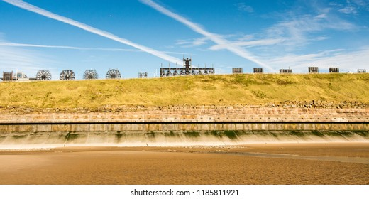 Aircraft vapour trails cross a brilliant blue summer sky above Blackpool Beach and the Blackpool Illuminations tableaux of Bispham Cliffs.