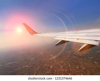 Aircraft wing in front of sky during a fly. Bright sun on horizon