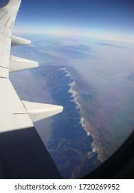 Aircraft wing and hazy mountains