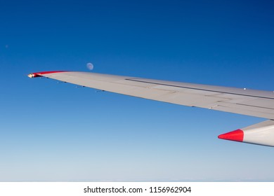 Aircraft wing with moon and blue sky taken from aircraft window
