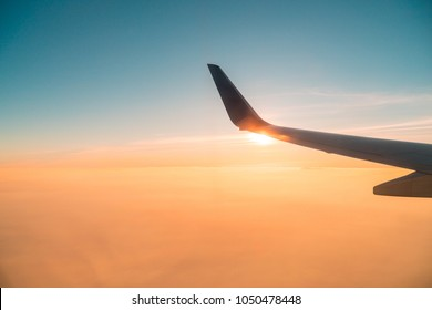 aircraft wing with sunset sky,scenic outside windows,sunnet in the air,looking through aircraft window.