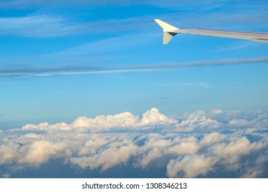 aircraft wing under blue sky in sunrise