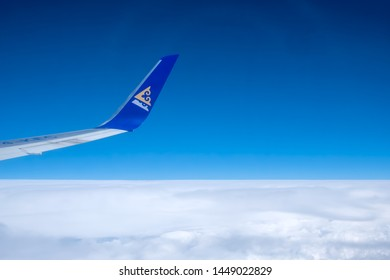 Aircraft's wing with Air Astana logo on a sky background. Air Astana plane is flying above clouds. 8 June 2019 Almaty, Kazakhstan.