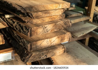 Air-drying sawn wooden plank slab pile under canopy at home backyard prepared for carpentry diy hobby. Woodshed store at house yard. Timber material stacked for woodworking