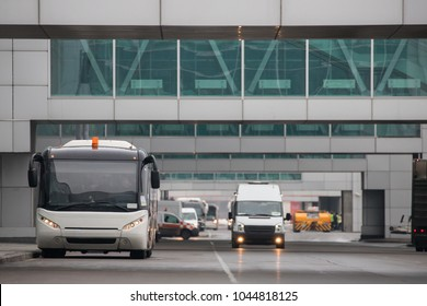 Airfield bus while driving through the airport, front view/Shuttle bus for transportation of passengers at airport terminal/Aviation services, transportation concept/