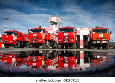 Airfield fire trucks with reflection in a puddle near garage boxes