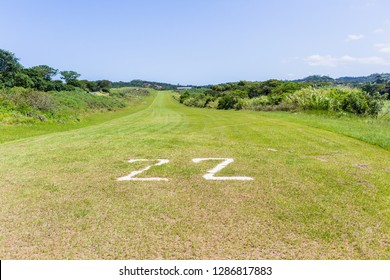 Airfield grass airstrip runway in countryside for light planes among farmland landscape.