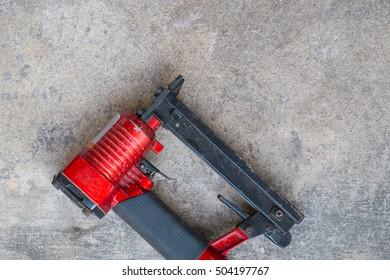 airgun on cement background, pneumatic staples on cement background
