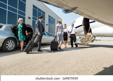 Airhostess and pilot greeting business people before boarding private jet