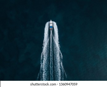 Airial foto of a speed boat passing by on a lake creating a beautifull riiple on the water