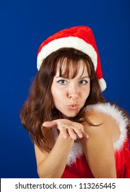 Air-kissing   girl in christmas costume over blue background